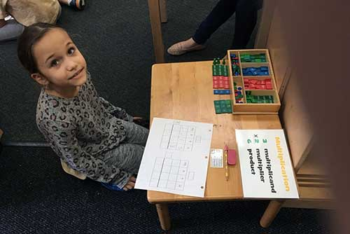 A lower elementary girl sits in front of her multiplication work