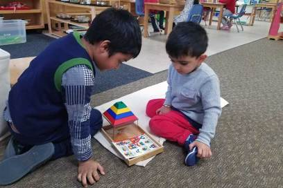 Two preschool boys work together as they sit on the floor