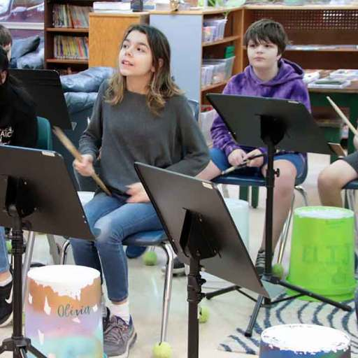 A group of upper elementary students sit in front of their bucket drums, drumsticks in hand.