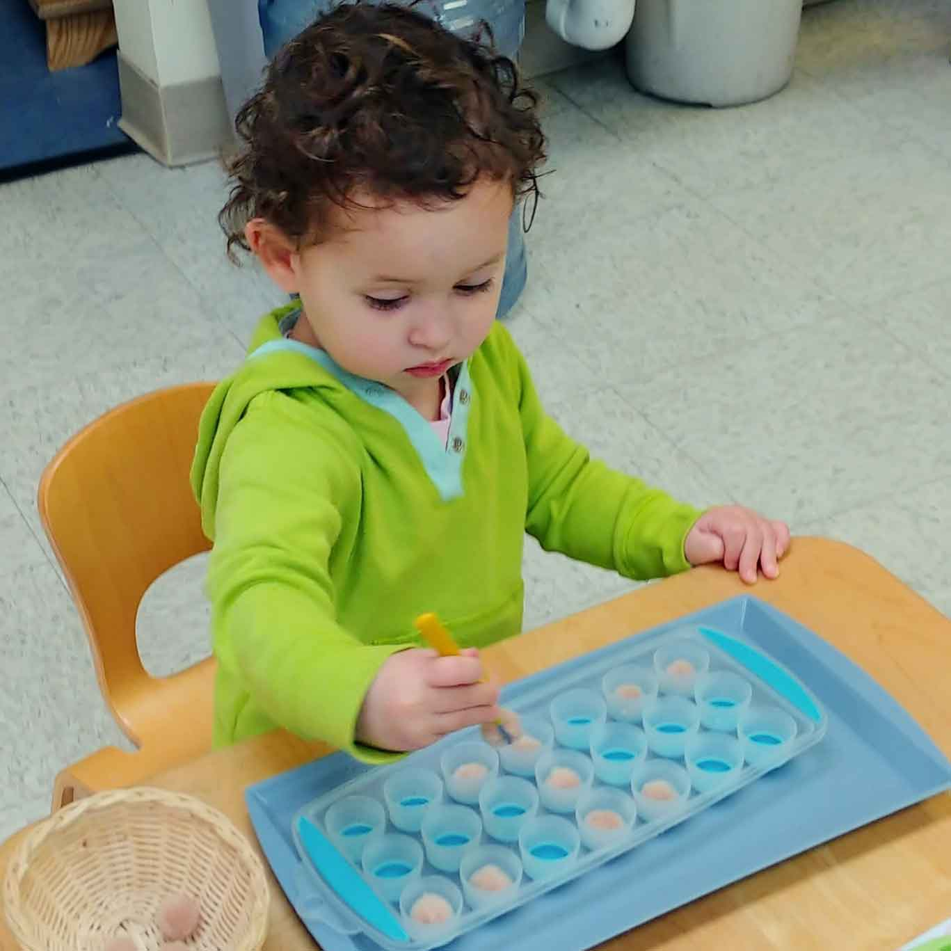 A toddler concentrates on transferring an item from a basket to a small cup