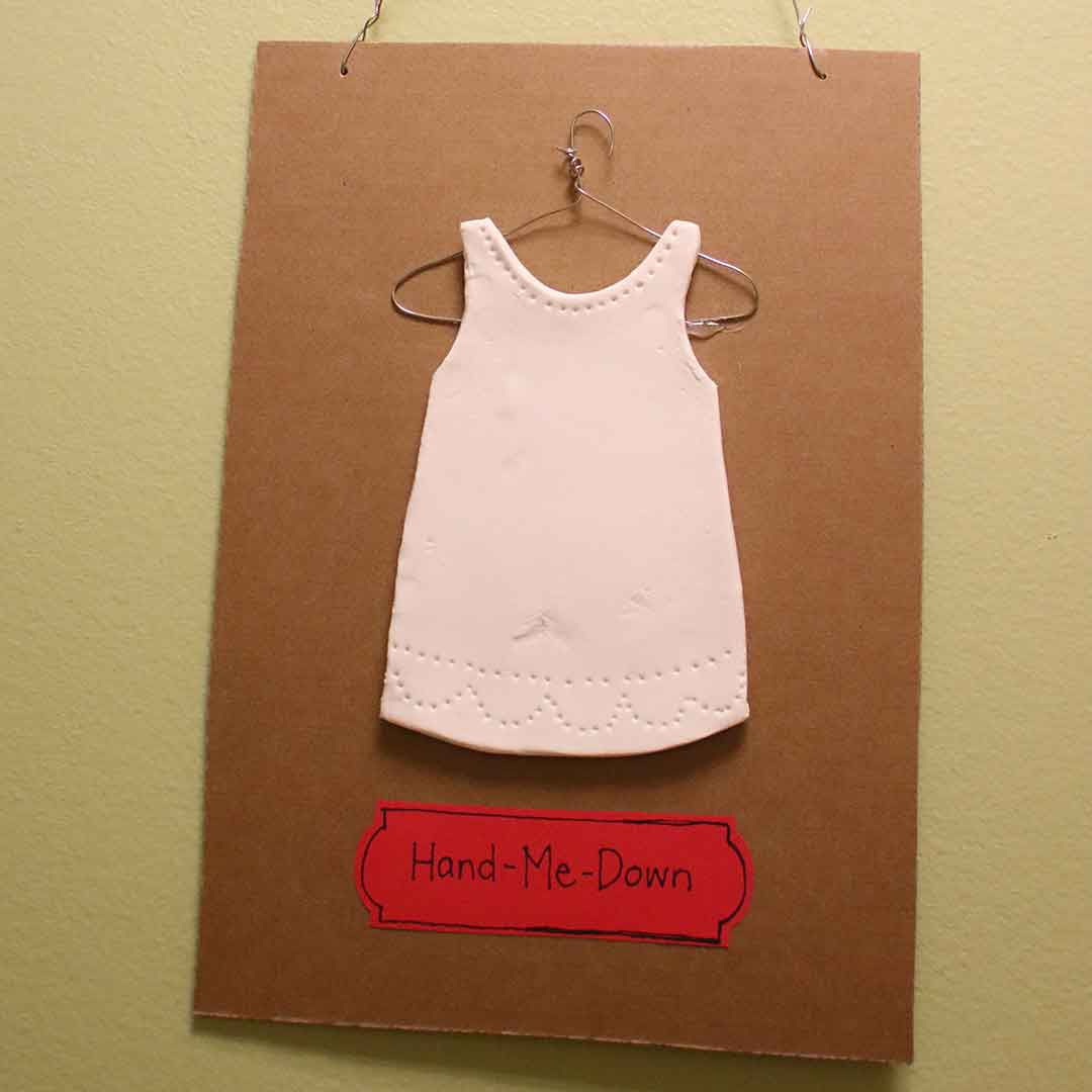 A flat plaster rendering of a dress, on a wire hanger