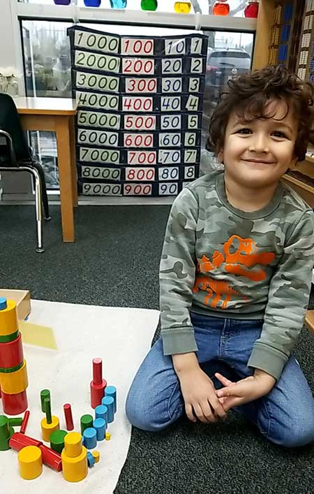 A preschool boy smiles beside a series of colorful wooden rods