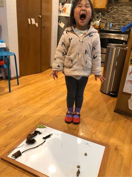 A little girl exclaims excitedly behind a board of items