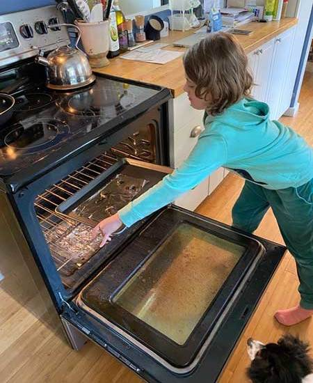 A girl carefully removes a pan of baked clay bats from the oven