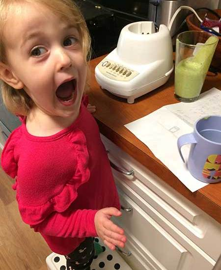 A toddler is excited about her green smoothy