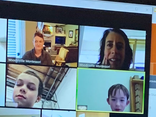 Two teachers and two elementary boys appear in insets on a video conferencing call.