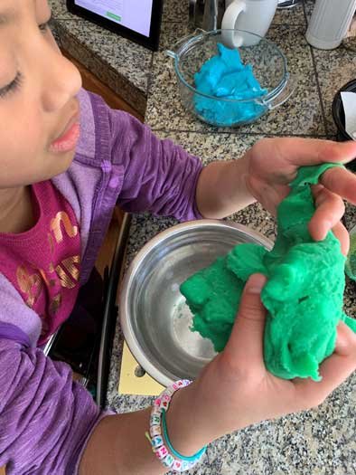 An elementary girl kneads a thick kelly green substance over a metal bowl