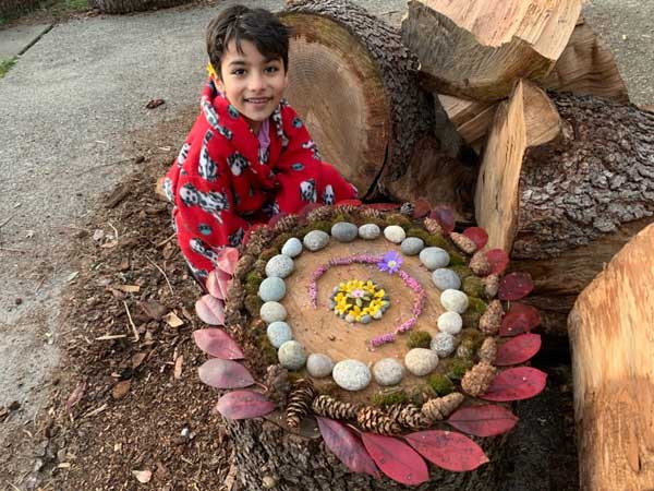 A student with a large mandala made with items from nature