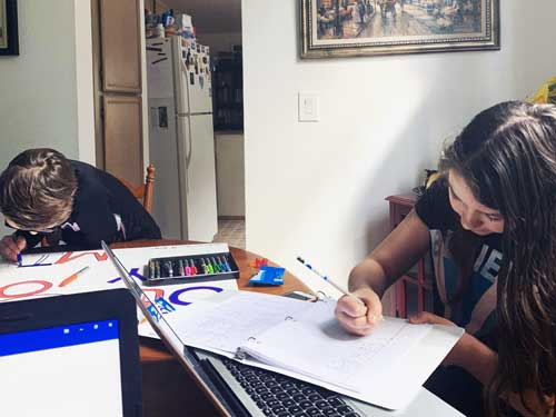Elementary boy and girl intently work on their assignments