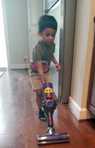 A toddler vacuums a hallway