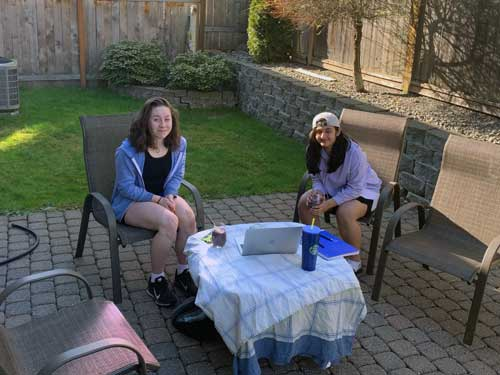 Two high school girls sit feet apart, with a laptop on a table