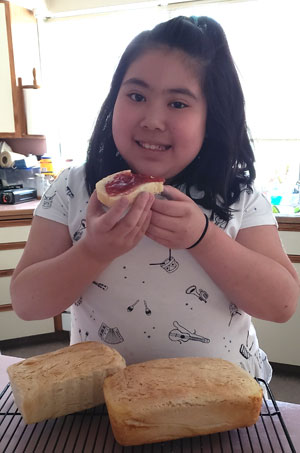 A girl eats bread and jam
