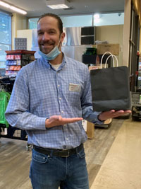 A store manager holds a paper bag on one palm