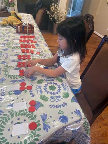 A preschool student lays out poker chips to represent numbers