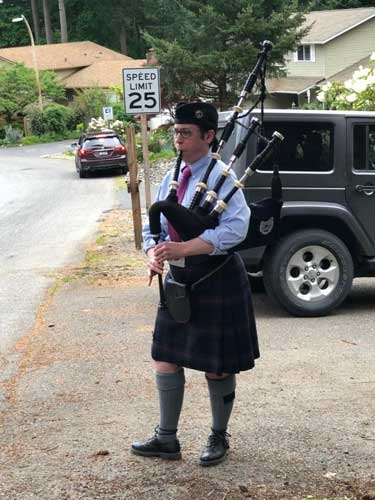 A woman in a kilt, button-down shirt, tam and knee socks plays the bagpipes