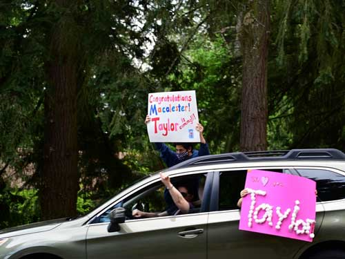 A car drives by with two signs out the window Congratulations, Macalester, Taylor said yes and Taylor