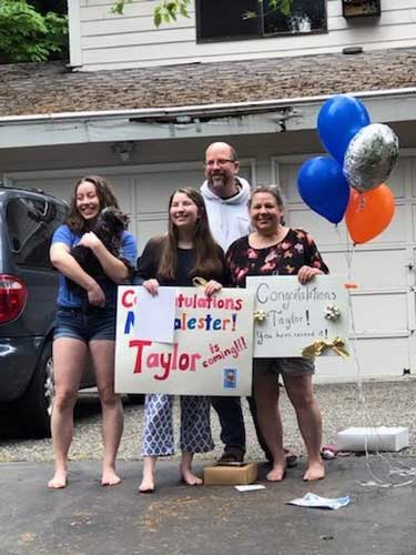 The entire family is all smiles with signs and balloons