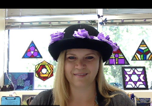 A teacher in a black brimmed hat with purple flowers