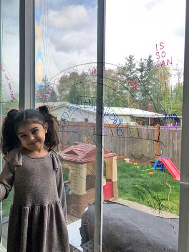 A girl smiles beside a sliding glass door, on which she's drawn a rainbow