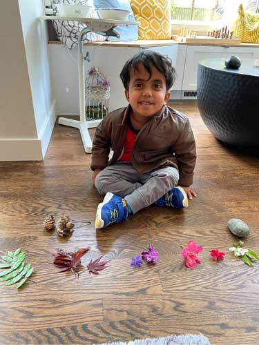 A boy sits beside various leaves and flowers in rainbow colors.