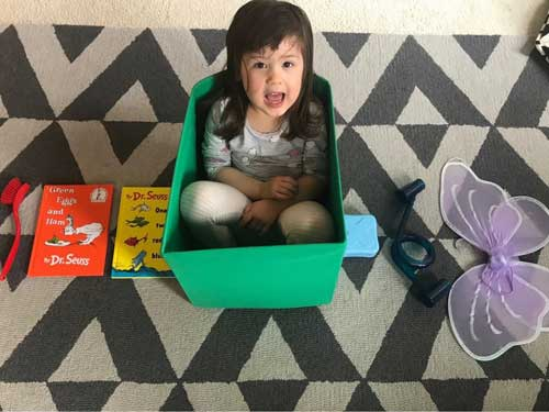A girl sits in a green box in the middle of rainbow-colored items, including books and toys