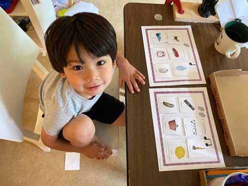 A child looks up from sorting words by number of syllables
