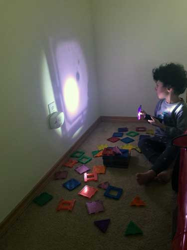 A toddler reflects lavender light on the wall with a lavender filter