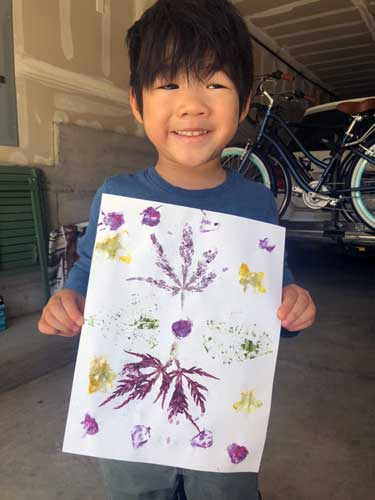 A boy holds his art work, purple and gold impressions of botanical specimens.