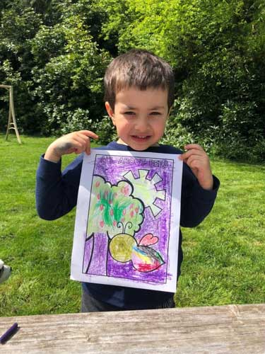 A preschooler holds up his colored page showing a bee, a tree and the sun.