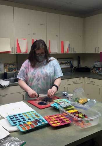 A woman breaks up old crayons, with colorful shapes in pans around her