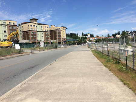Apartments on the left, a street, broad sidewalk and chain link fence on the right.
