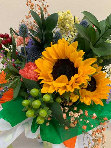 A flower arrangement featuring sunflowers
