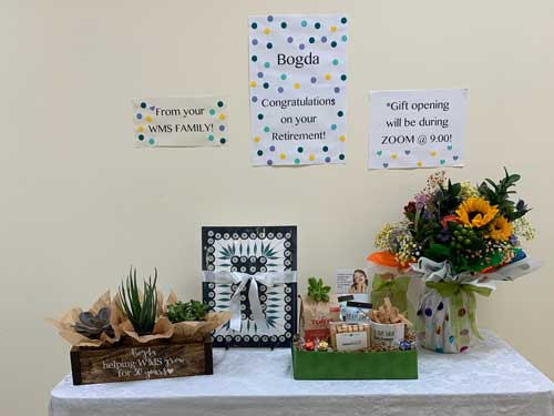 A display of gifts on a table, with well-wishes on a wall.