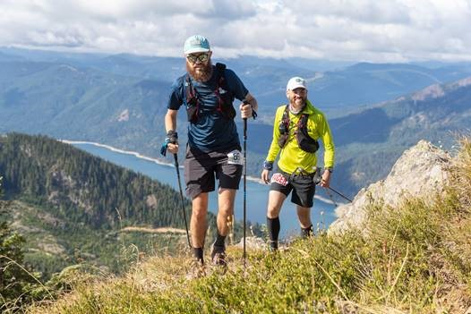 Two mean hike up a mountain ridge in running gear, with hiking poles
