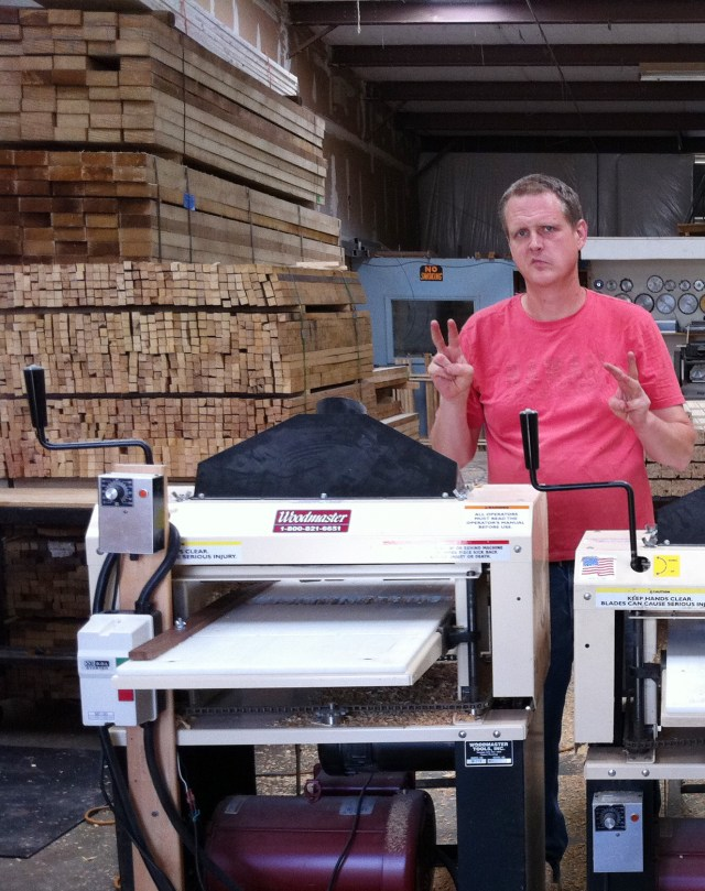 "Bill and Andy do some serious production with their Woodmasters. Behind Andy are stacks of stakes they manufacture, stacked and ready to go. Andy hand signal says, ""This is the second of our three Woodmasters."""