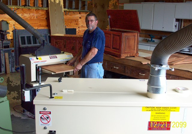 "Here's Charles in his workshop, running a panel through his Woodmaster Molder/Planer while his Woodmaster Drum Sander stands ready (foreground). Behind Charles are two of the toy boxes he's made for his grandkids. He has his work cut out for him: when we spoke, he had 13 grandkids, ""And one on the way!"""