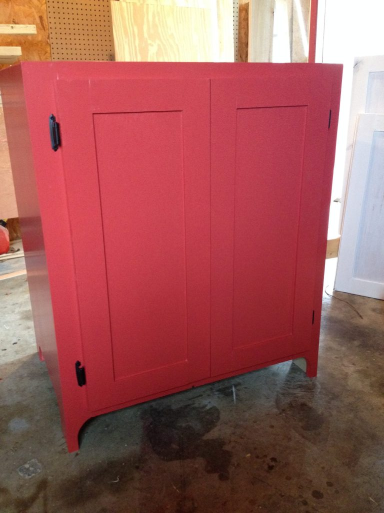 Small red cabinet with shaker cabinet doors