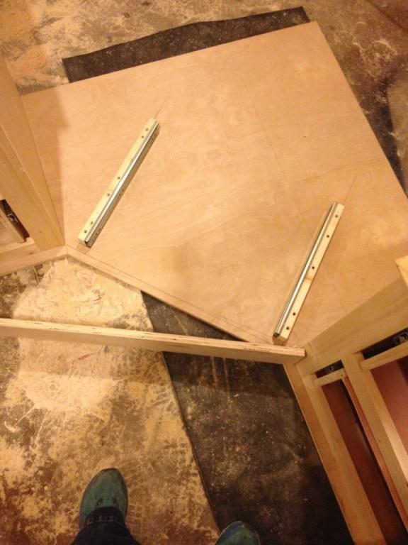 Middle corner desk drawer support blocks installed into bottom of desk top