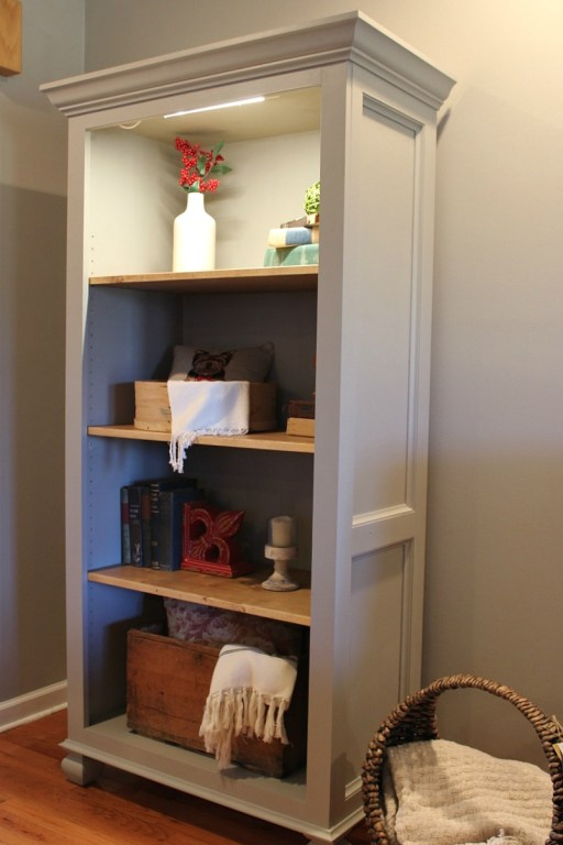 Stand alone bookshelf in living room decorated with old books and vases