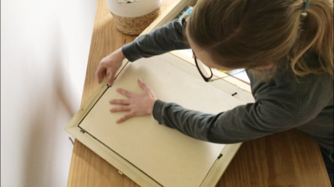 Shara placing picture frame backer onto box lid
