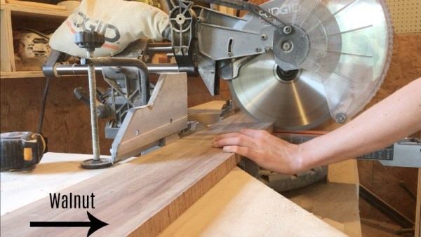 trimming walnut board to length on miter saw