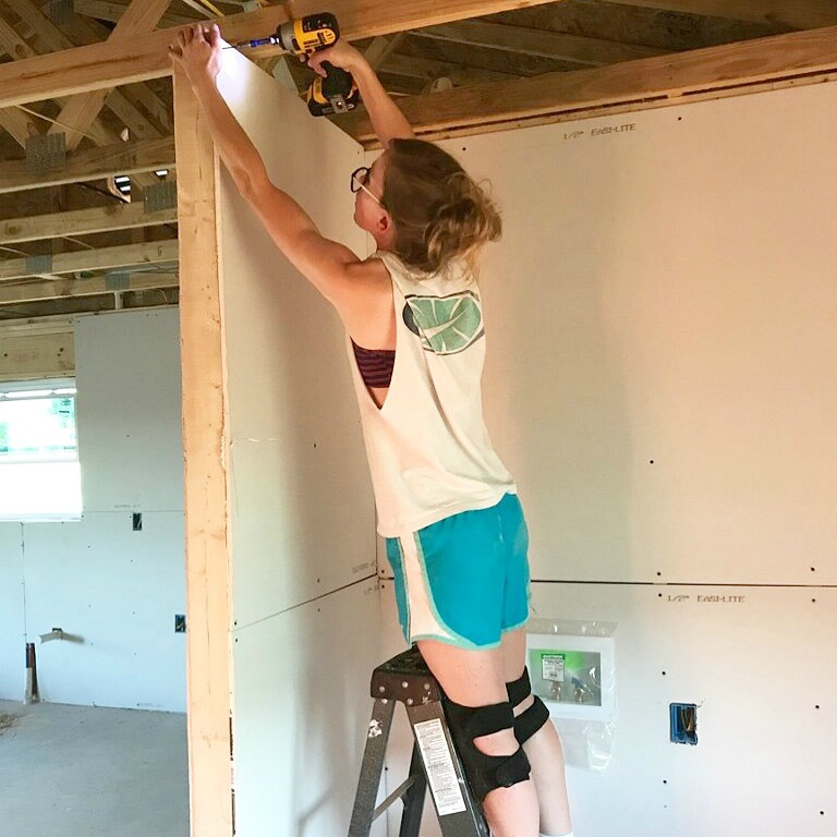 Shara Woodshop Diaries using small ladder to install drywall in laundry nook of garage apartment