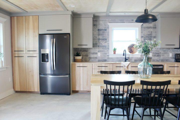Modern wood and grey kitchen with backsplash tile and black stainless refrigetator