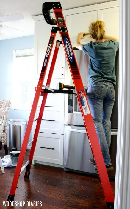 Using ladder to install cabinet hardware in kitchen cabinet doors--gift idea number 10 for new homeowners