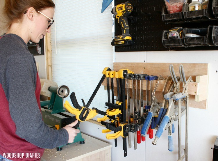 Shara Woodshop Diaries hanging clamps onto DIY clamp rack in workshop