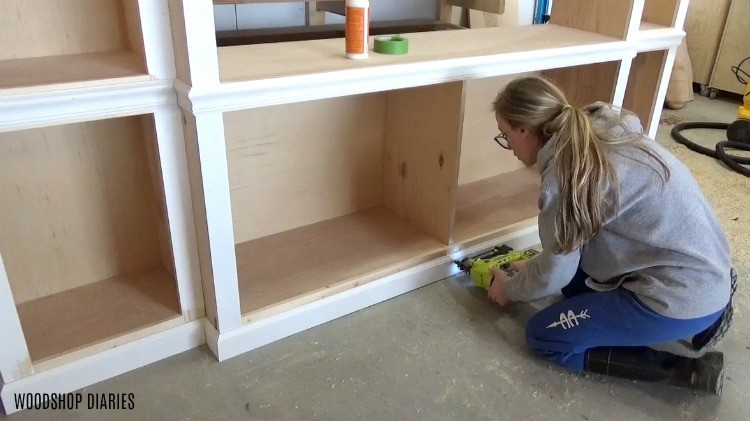 nail baseboard onto middle DIY entertainment center cabinet bottom