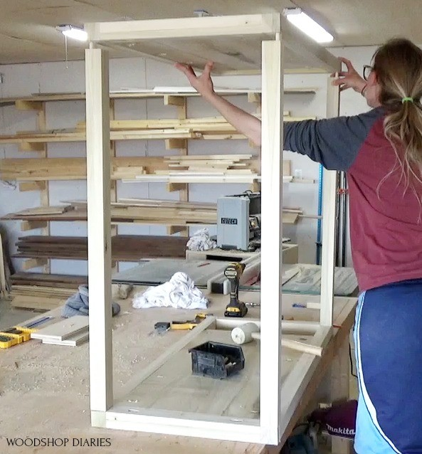 Shara installing side panel onto dresser frame on top of workbench--using wood glue and dowels to assemble