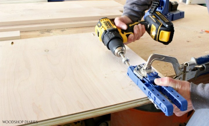 Kreg 320 jig clamped to plywood panel with drill drilling pocket hole