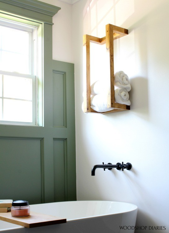 Close up of scrap wood towel rack hanging on wall above bathroom in renovated bathroom