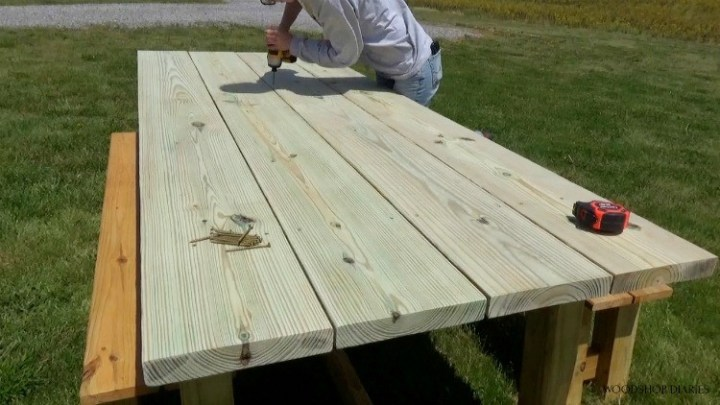 "Attaching 2x10 treated boards to trestle table base frame using 3"" wood screws"